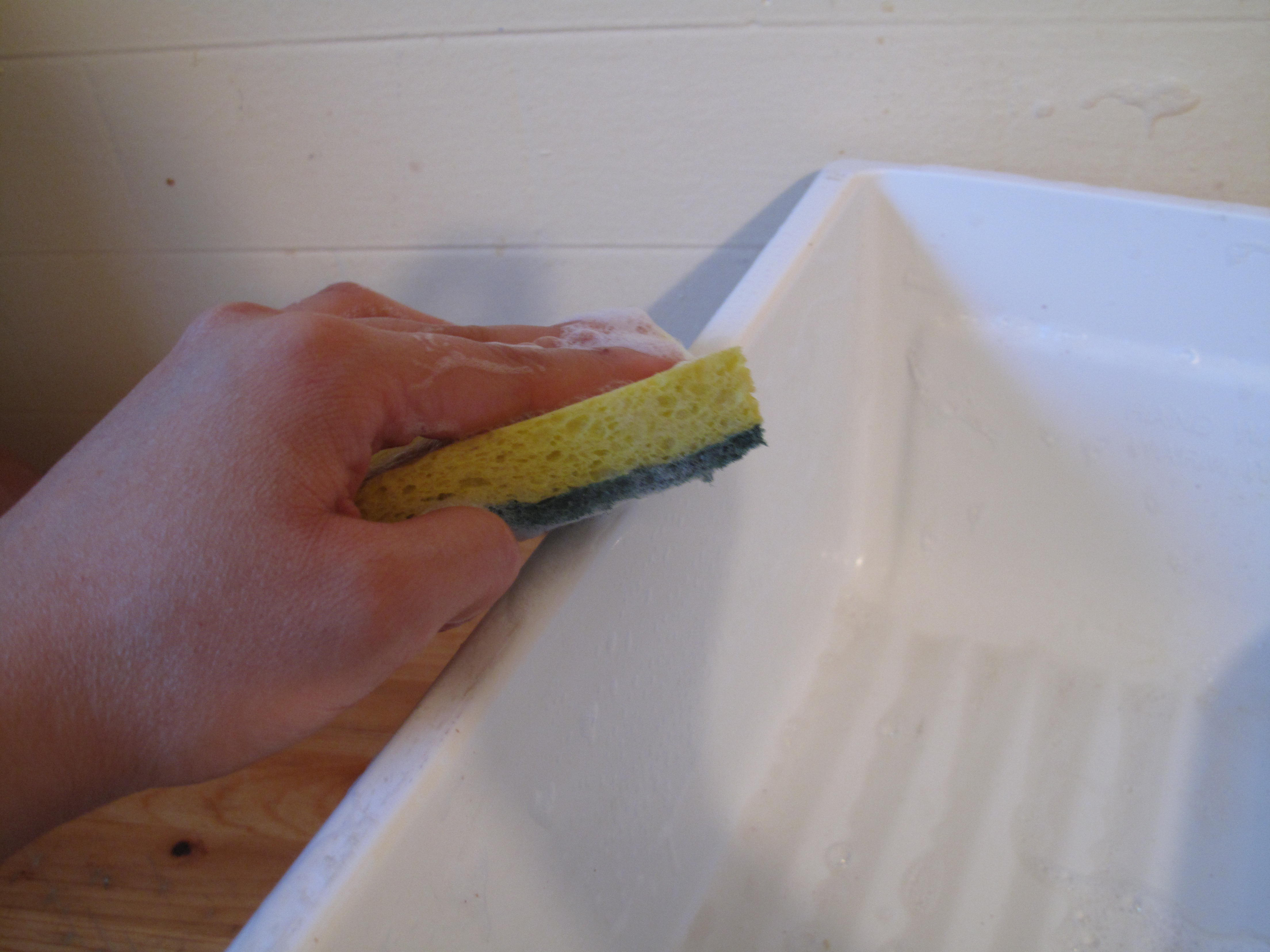 Remove crisper drawers completely from the refrigerator and scrub them clean with dishwashing detergent and hot water.
