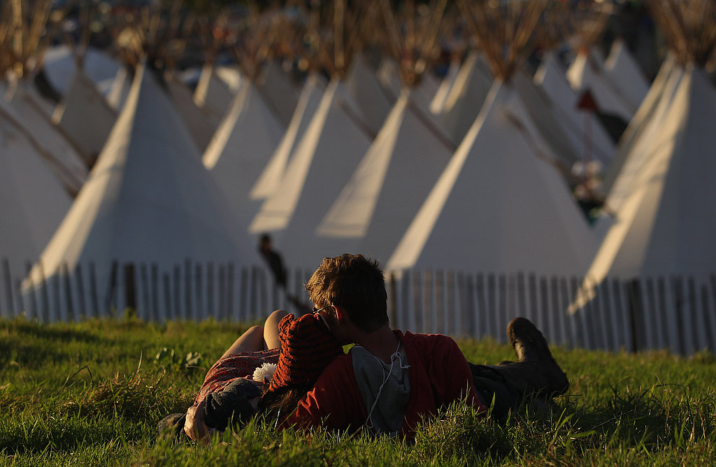 These lovebirds watched the sunset together on the grass at the Glastonbury festival.