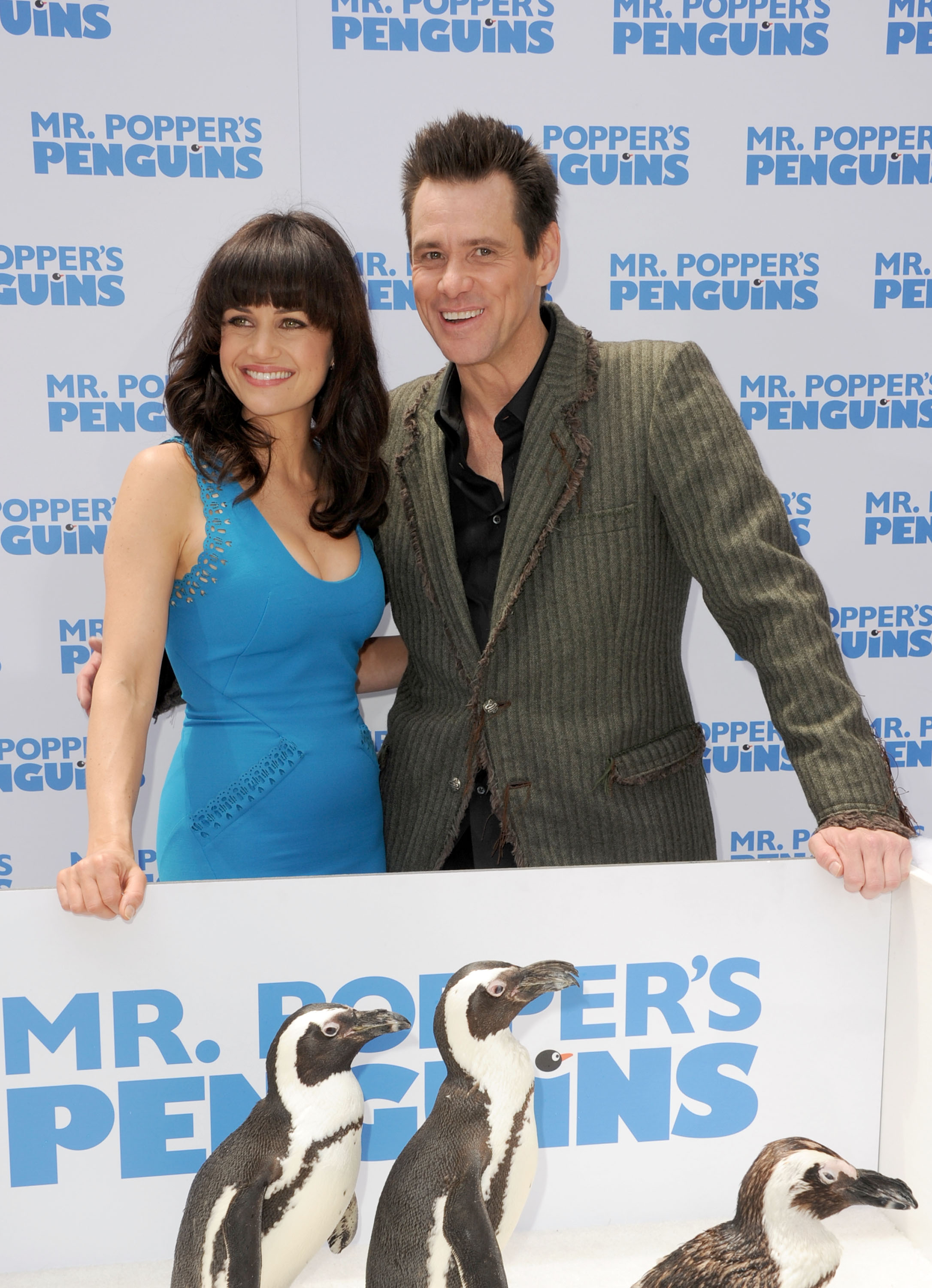 Carla Gugino and Jim Carrey get a chilly welcome from some tuxedoed friends at the 2011 premiere of Mr. Popper's Penguins.