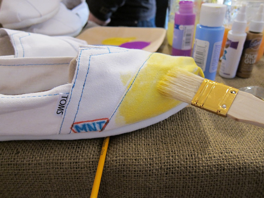 """Associate editor Marisa Tom also started with a yellow base and added her initials with colorful Sharpie markers on the side of each shoe. Our Tips For Decorating:   Keep a mason jar filled with water at the ready. We found that diluting our paint colors just a little helped the application process. By watering down the vibrancy, you can manipulate the color scheme to your liking. This is particularly useful if you're going for a tie-dye or ombre effect.  Thicker brushes are way easier to work with — trust us.  There's really no such thing as messing up here. Improvisation (and embracing it) made this project super fun and inspired a bright, unexpected outcome, which we loved.  Make sure to keep the """"stuffing"""" of the shoe in place while you paint and as the shoe dries. This way, your shoe will keep its signature TOMS shape."""