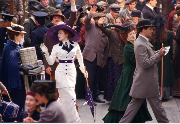 A grand entrance onto the boat — how glamorous the whole thing looks. We love the ultra-feminine silhouette of her fitted jacket and skirt — not to mention the whole glove-and-hat thing.