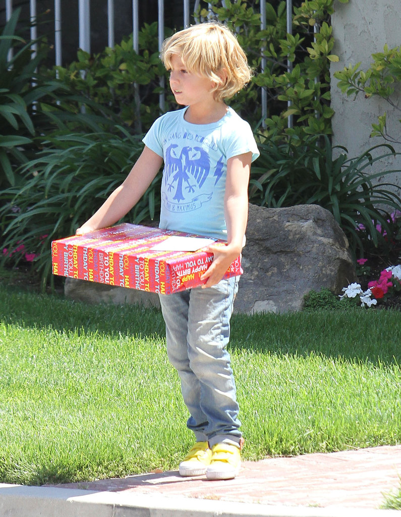 Kingston Rossdale carried a gift to a birthday party.