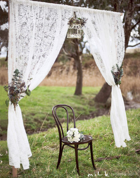 Dainty lace curtains, natural arrangements, and a delicate white birdcage create a rustic, elegant vibe. Photo by Mile Photography via Style Me Pretty