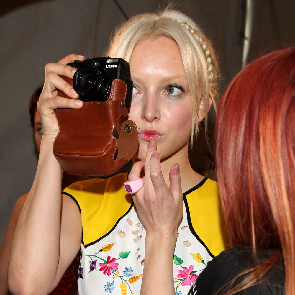 A model takes a snap while having her lip colour touched up.