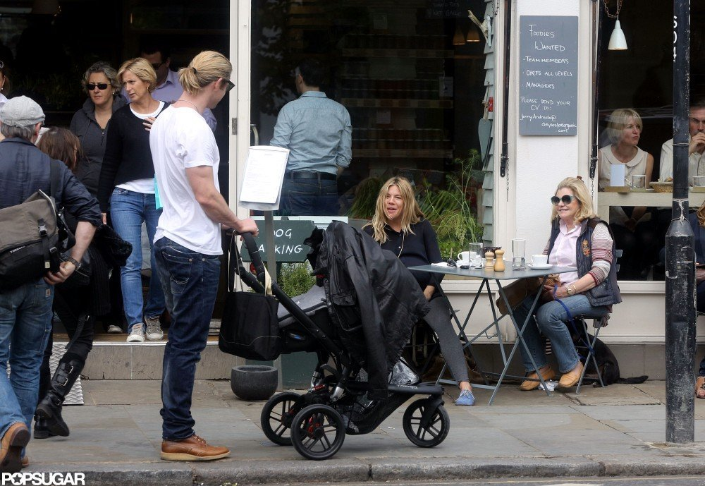 Chris Hemsworth pushed baby India in a stroller and chatted with Sienna Miller while waiting for his wife Elsa Pataky in London.
