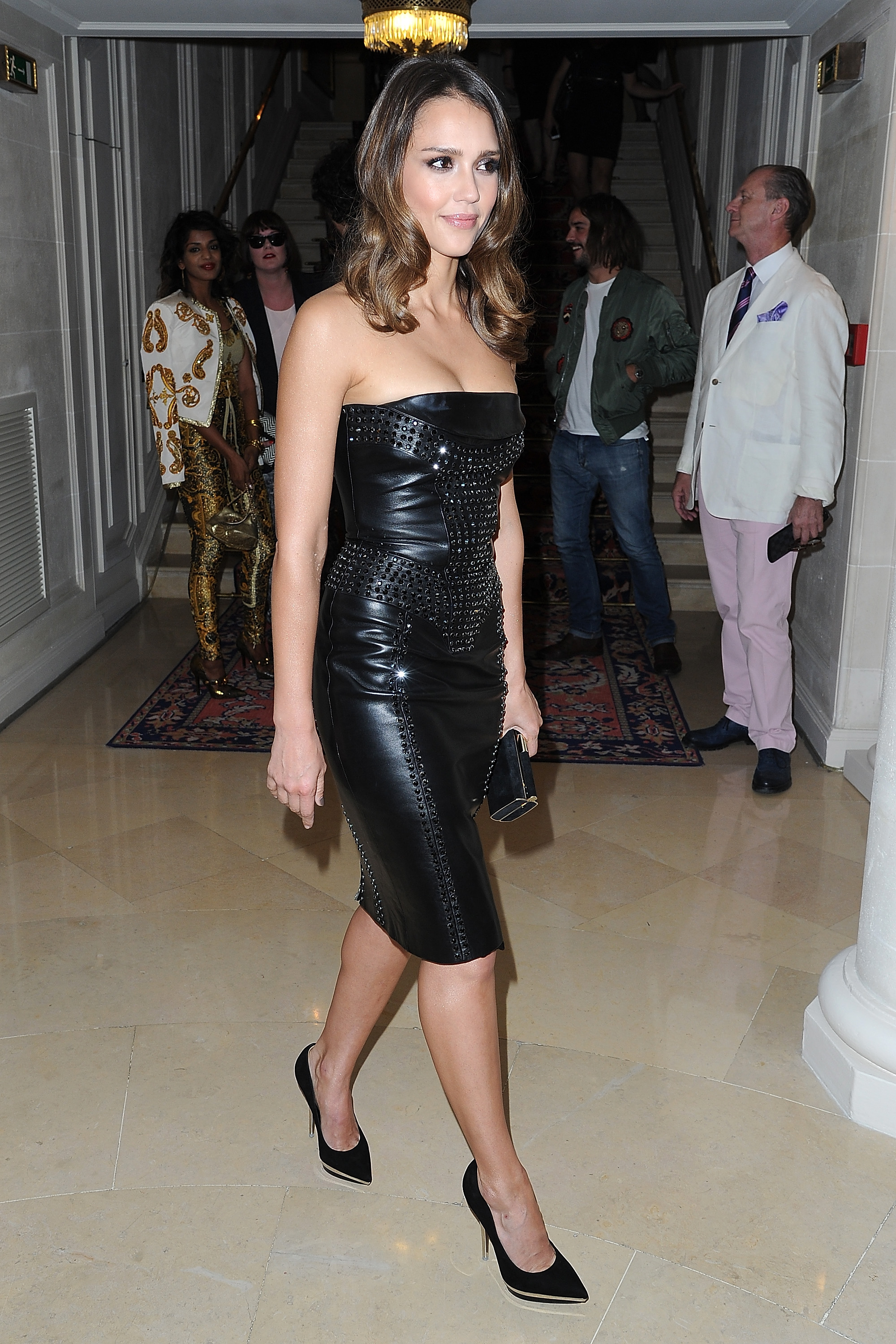 Jessica Alba showed off her curves in a tight black leather dress for the Versace show for Paris Fashion Week.