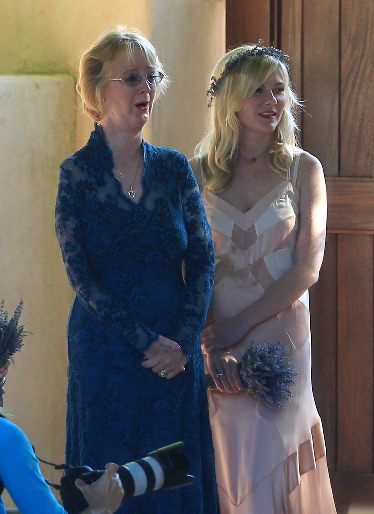Kirsten Dunst looked on as the bride and groom took pictures.