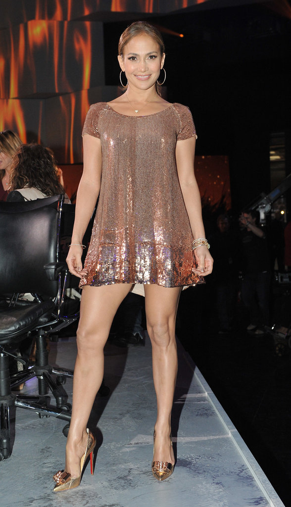 Jennifer Lopez showed off her stems in a sequined Randi Rahm mini and coordinating golden Louboutins.