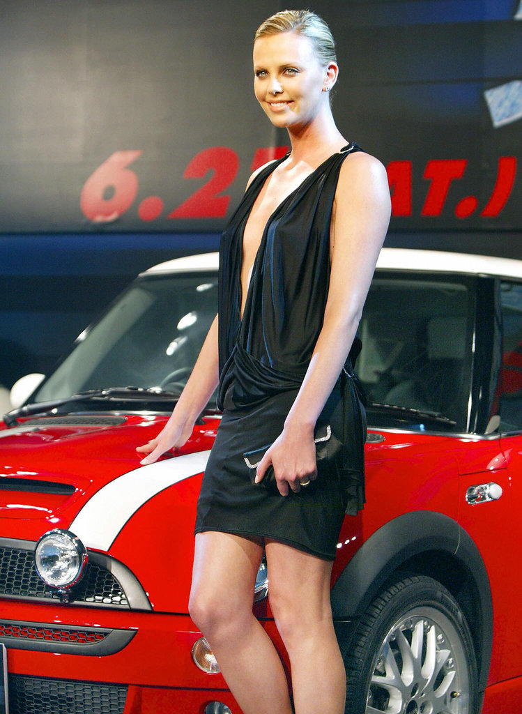 Charlize wore a sexy black minidress as she posed with a Mini Cooper at the Tokyo premiere of The Italian Job in June 2003.