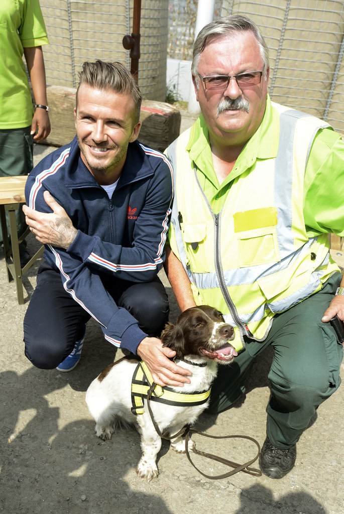 David Beckham posed with a security guard and his companion.