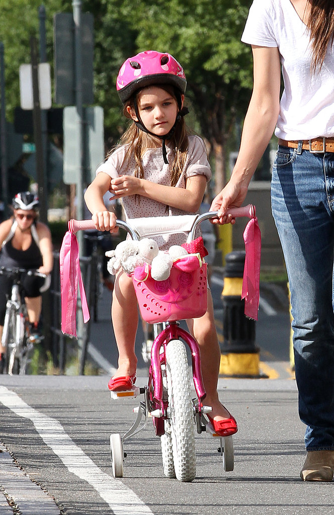 Suri adjusts her too-cute rolled up sleeves as Katie steers.
