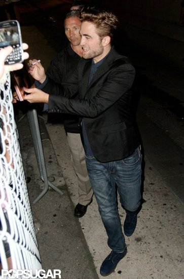 Robert Pattinson smiled and signed autographs for fans.