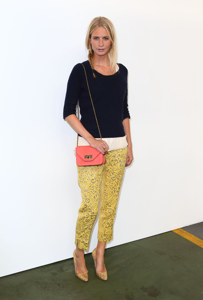 Poppy attended the House of Holland show in a navy blue Paul Smith cable-knit sweater, which she layered with a Rag & Bone top and yellow printed Dolce & Gabbana trousers. We love how she added a pair of gold Manolo Blahnik heels and a pretty pink Chloé shoulder bag.