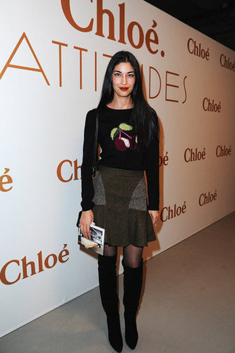 Caroline Issa offset a quirky printed sweater with a feminine ruffled-hem skirt and sexy knee-high boots.