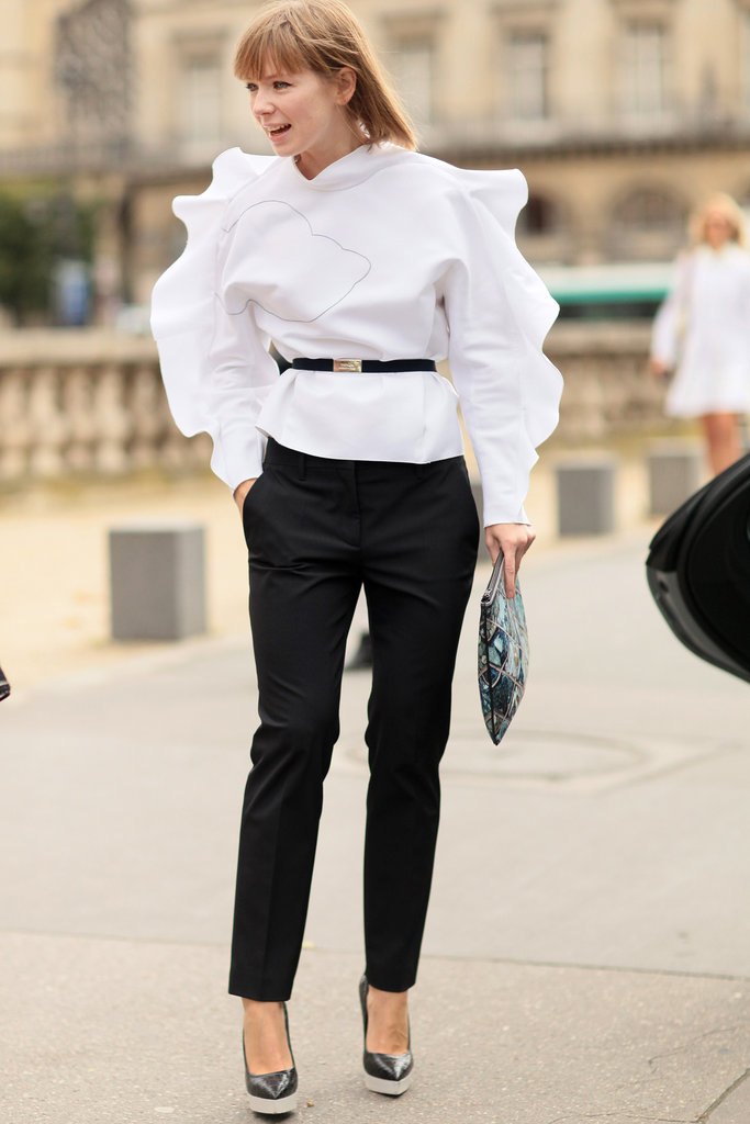 A ruffled blouse emboldens basic black trousers.