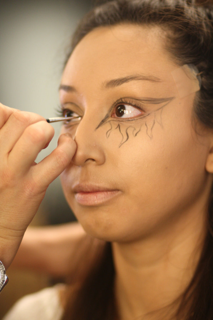 After evening out Lisette's skin tone with Pro Longwear concealer, Zizzo used Fluidline gel liner to sketch flames around her eyes.