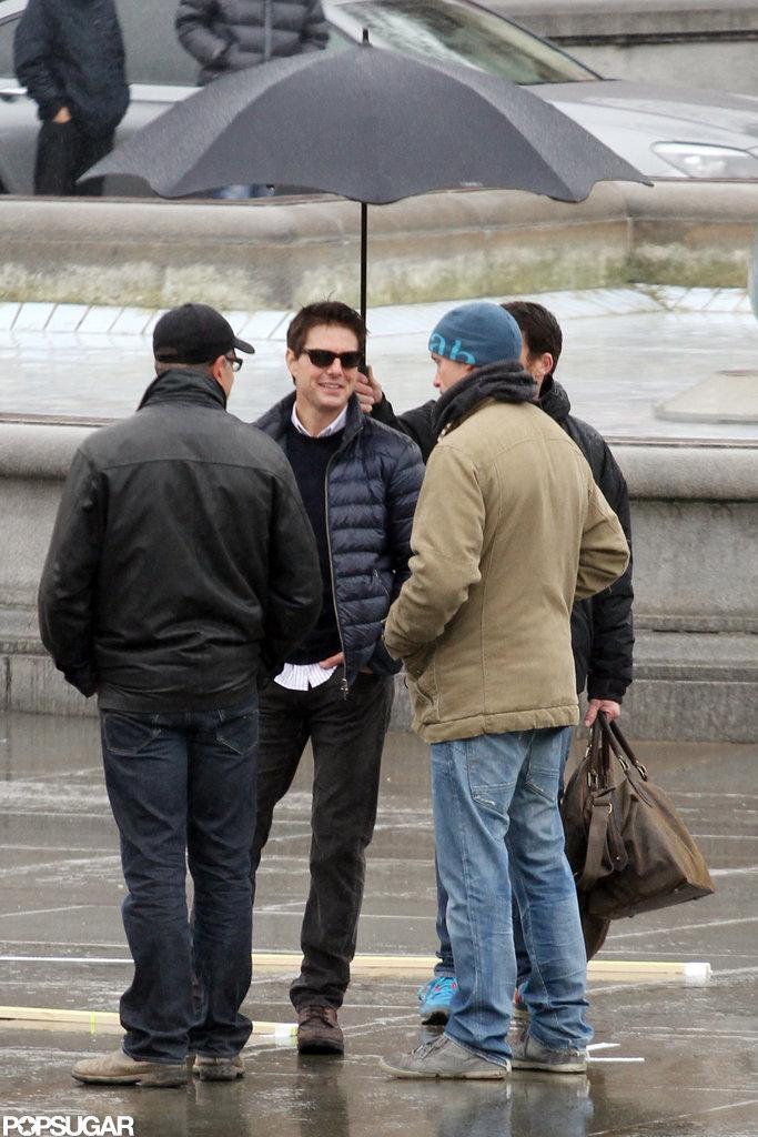 Tom Cruise stood under an umbrella in London.