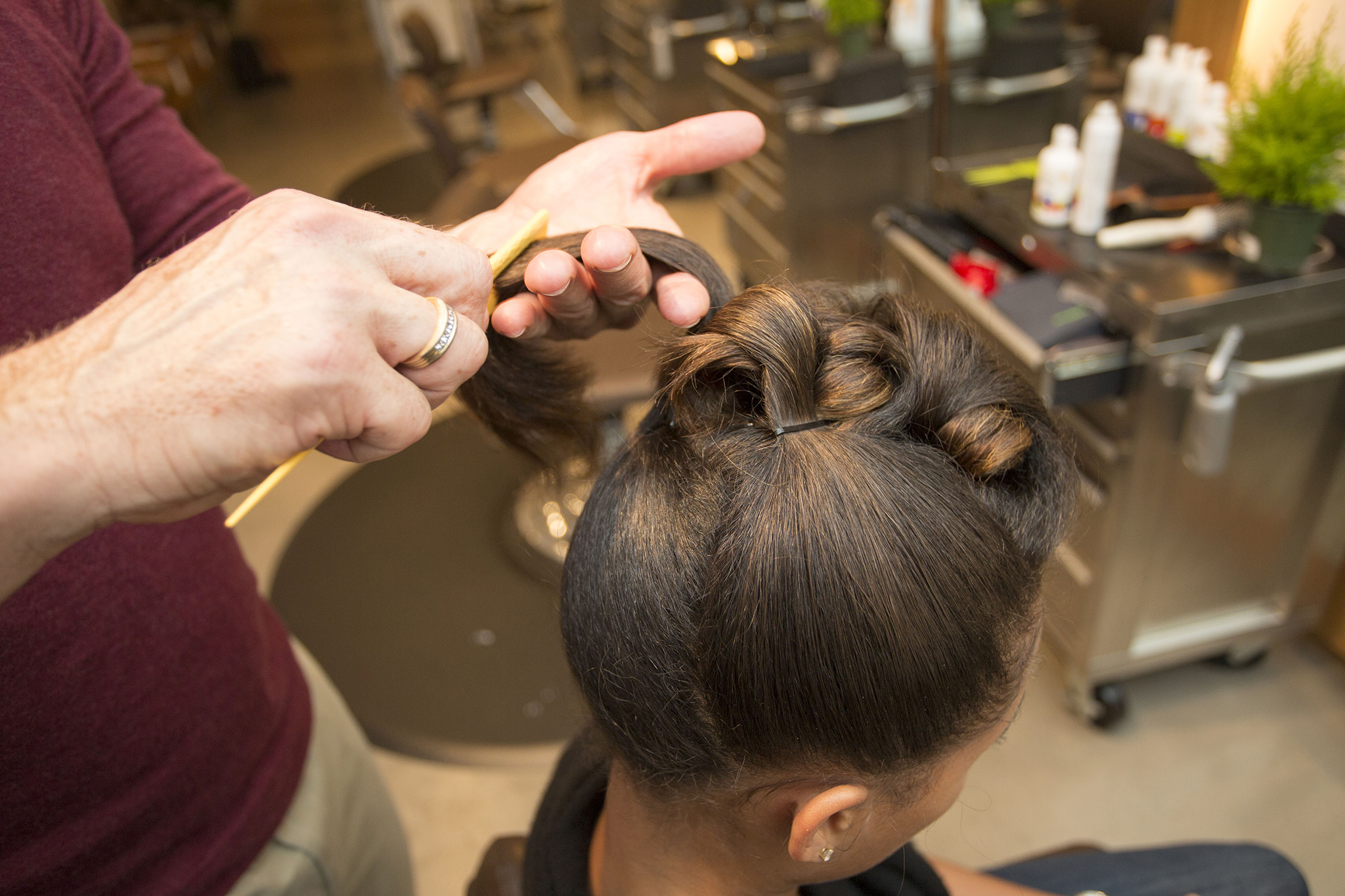 Finally, you want to sweep the sides and back upward. Make sure to secure the hair with a bobby pin first, then create the barrel curl and secure again.