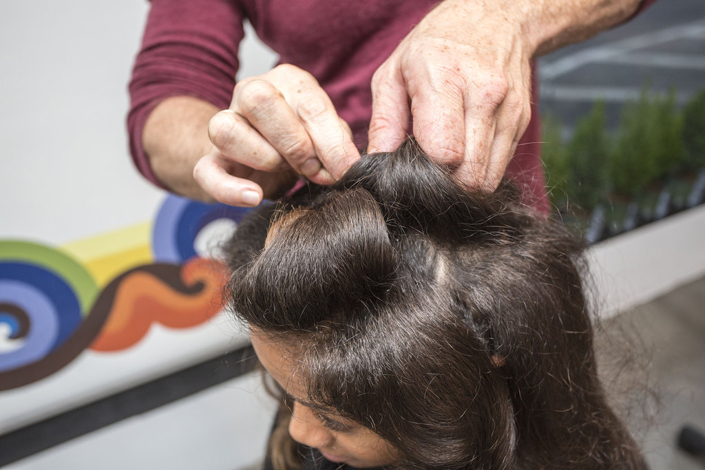 """""""One thing about textured hair is you can make shapes to get a seamless look,"""" Dickey explained. Starting in the front, take random sections and roll hair around two fingers to form a barrel shape. Secure with bobby pins.  Continue rolling sections (the majority of the curls should be toward the front of the face and bit off center)."""