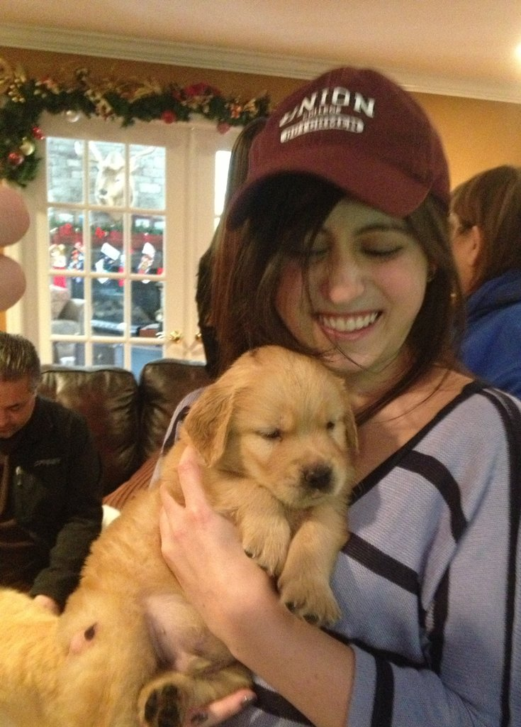 Marketing Intern Tess Koman cuddled with her newly adopted Golden Retriever puppy, Waffle.