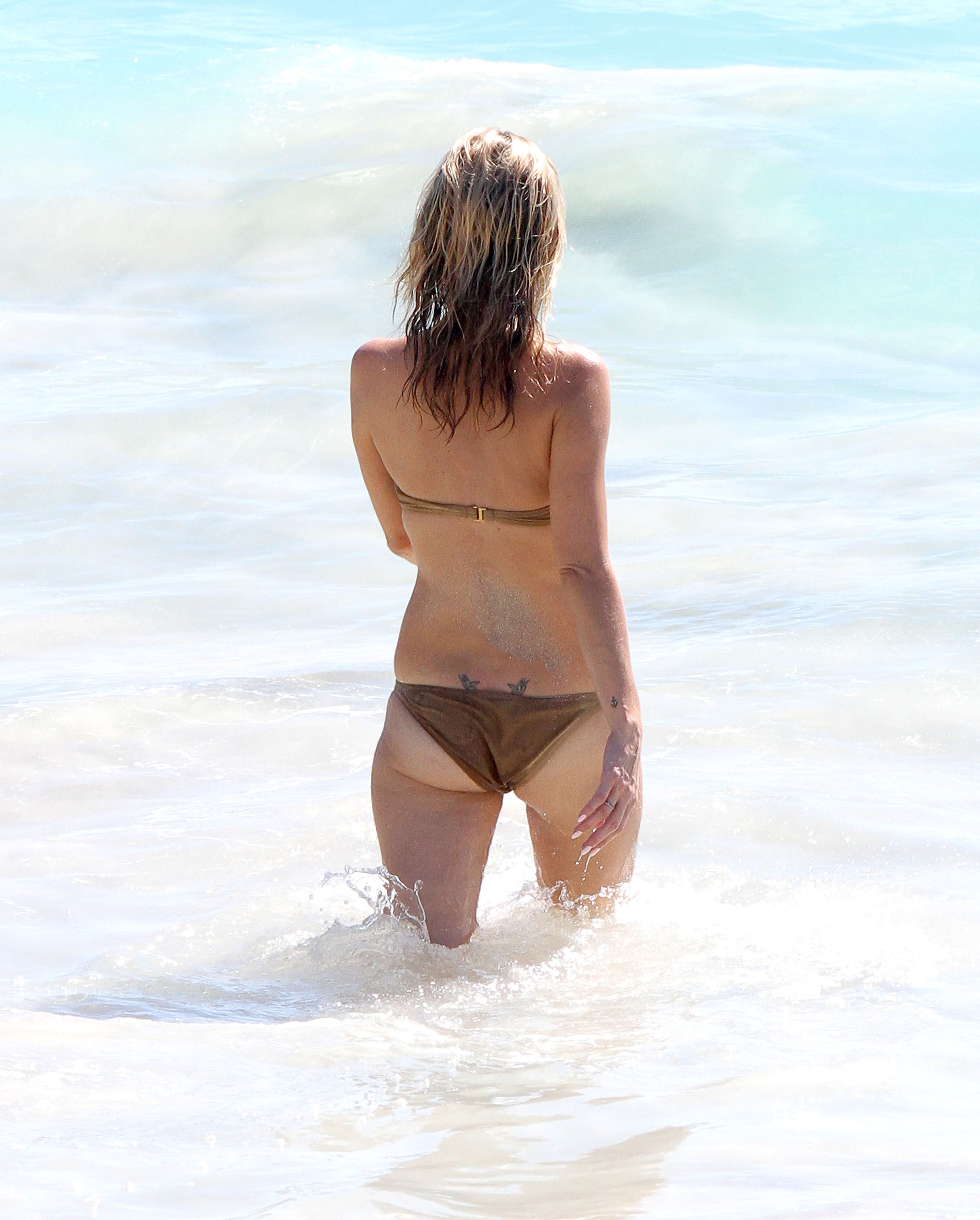 Kate Moss showed off her Lucian Freud tattoo on her lower back.