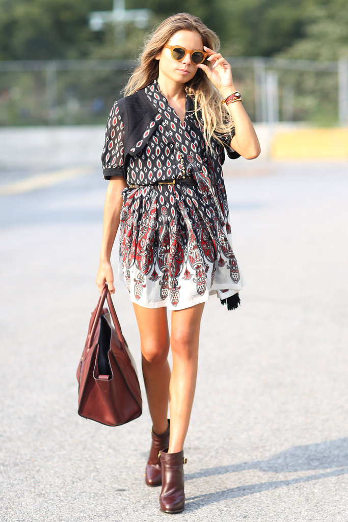 She's strutting her stuff in a printed dress and brown booties and carrying a red Céline bag.