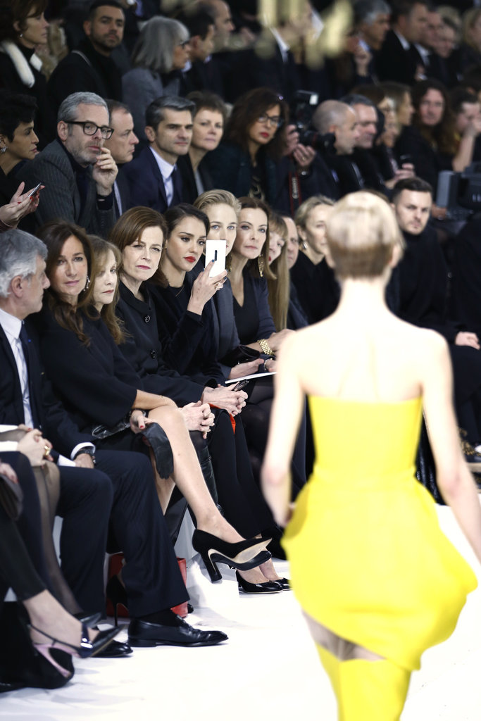Jessica Alba took photos from the front row at Christian Dior.
