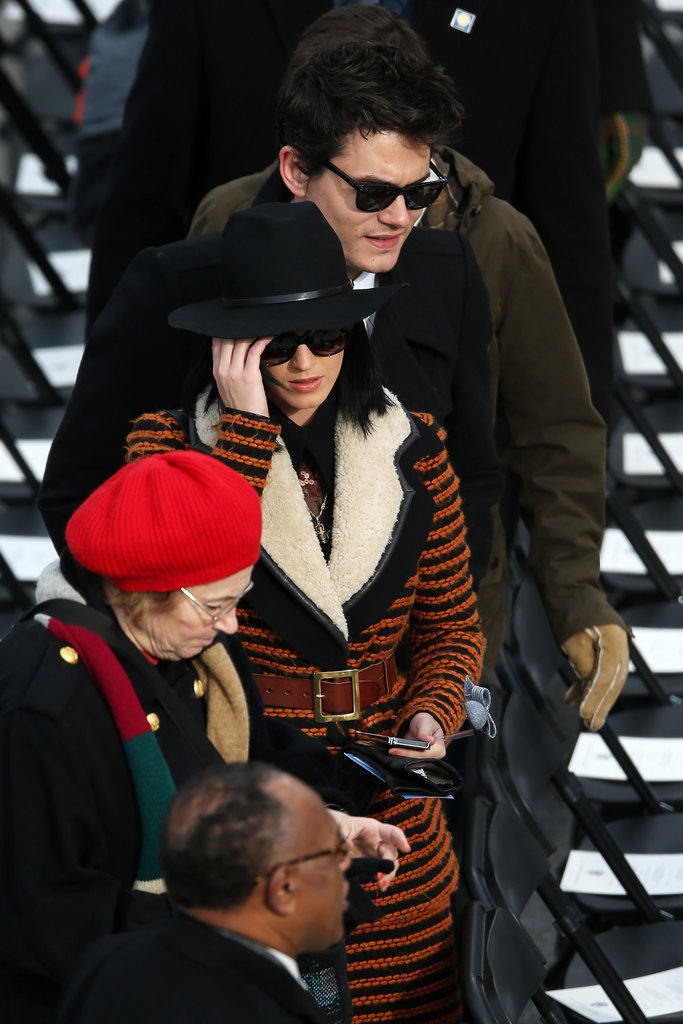 Katy Perry, along with John Mayer, stepped out at the Capitol in a rust orange and black striped and belted Rodarte coat and wide-brimmed fedora.