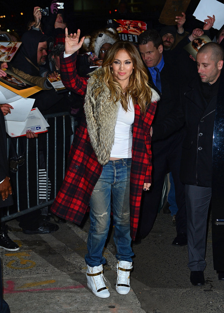 Jennifer Lopez showed off her sporty Winter style in a buffalo-plaid Michael Kors coat, ripped boyfriend jeans, and white Giuseppe Zanotti wedge sneakers.