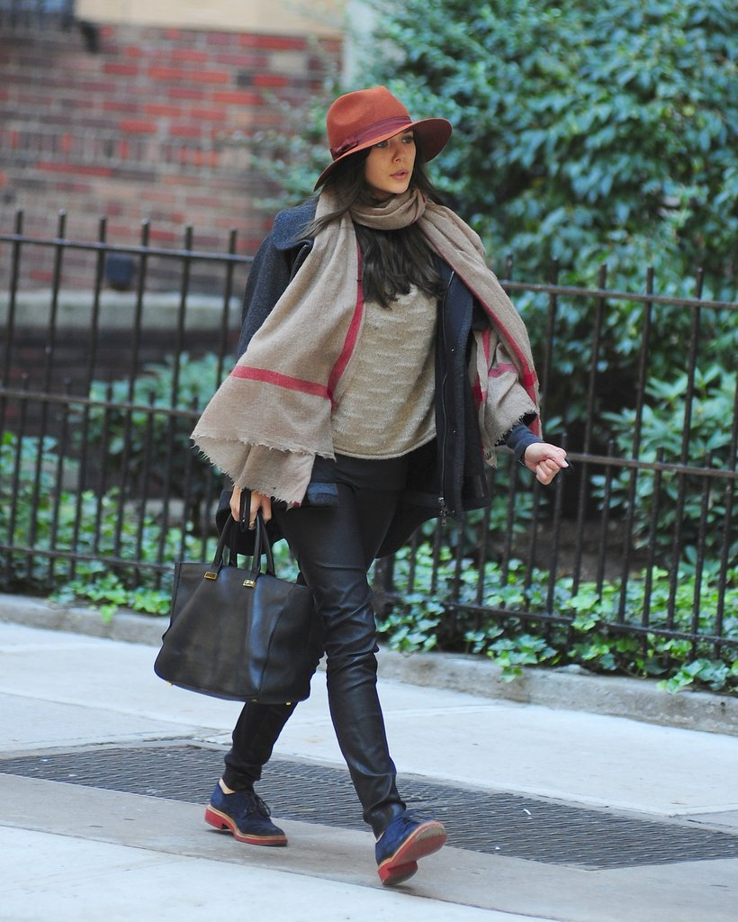 Elizabeth Olsen strolled NYC wearing a neutral ensemble with colorful accessories: a burnt-orange hat, a red-and-beige scarf, and navy oxfords.