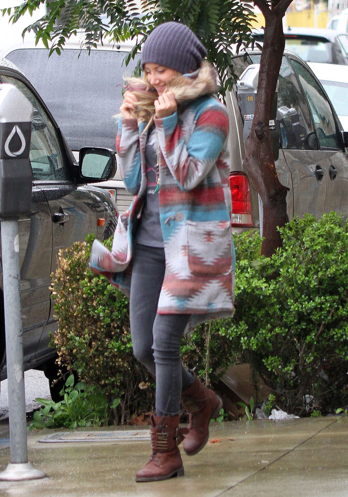 Ashley Tisdale bundled up in a printed coat, gray jeans, brown lace-up boots, and a gray ribbed beanie while out and about in LA.