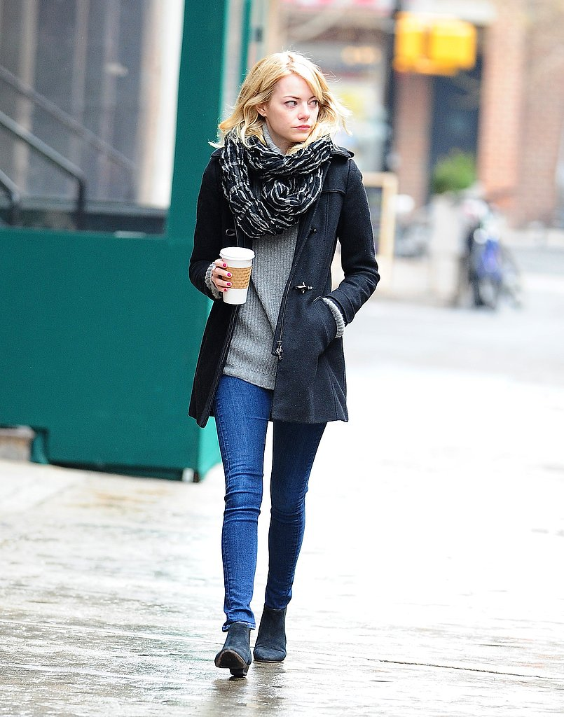 Emma Stone took a walk on the wet streets of NYC in a black toggle coat, a printed scarf, skinny jeans, and black booties.