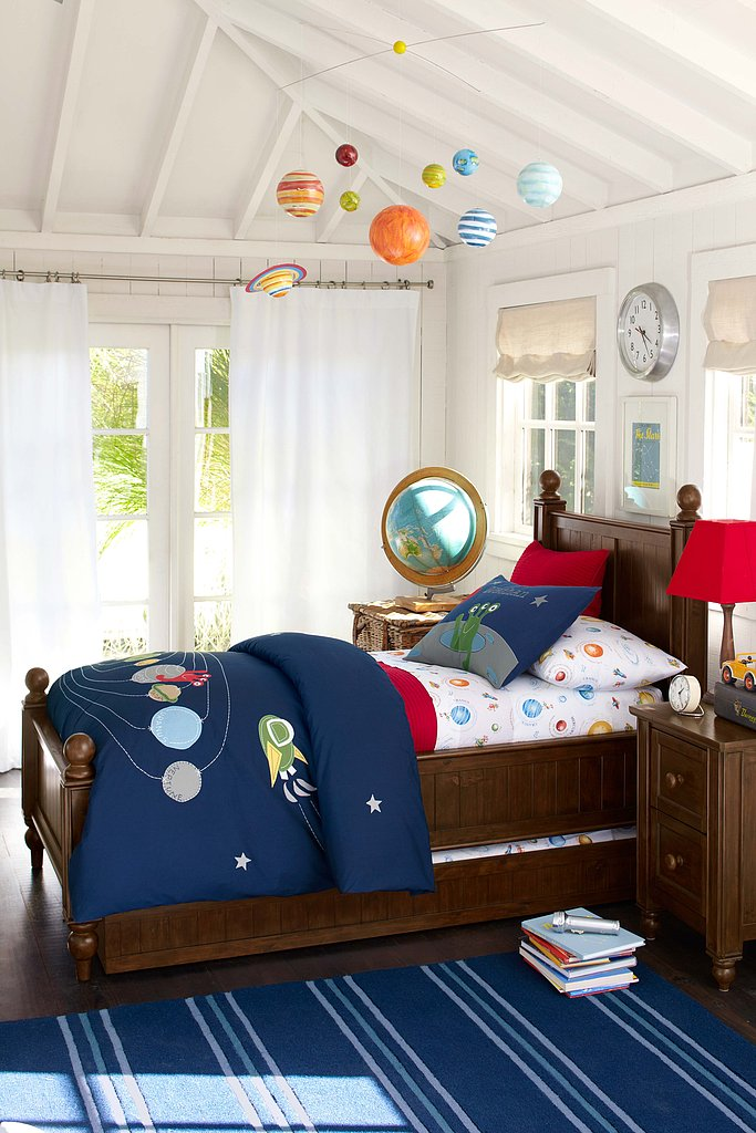 Your big boy's room may already be the final frontier when it comes to keeping a clean house, and now it can look like that even when it's clean. We love the new Nathan bedding collection complete with planets, stars, and even the requisite alien. What also drew me to this room is the solar system mobile hanging from the ceiling. Most mamas move away from mobiles when tots leave their cribs (or before!), but this one helps complete the room and carry the space theme up to the ceiling.