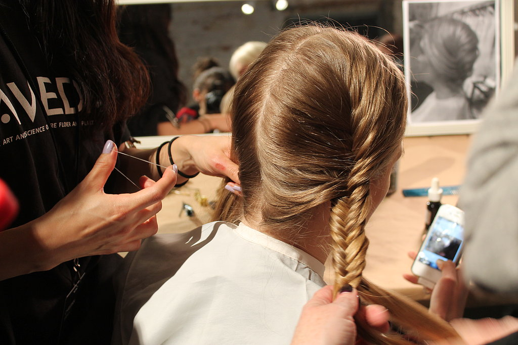 """""""It's simple, but it looks intricate,"""" Antoinette Beenders, Aveda's global style director, said. """"It fools the eye."""" The straightforward style started with a fishtail French braid on either side of the head. Once secure, Beenders pulled on the braids to fatten and texturize them before crossing them at the nape of the neck."""