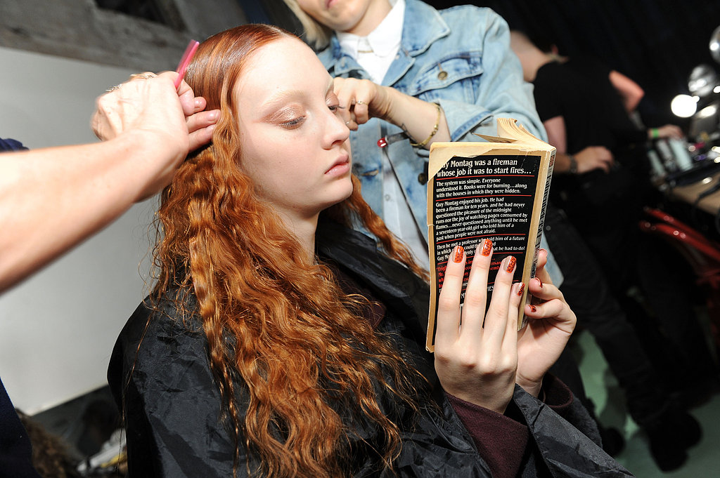 A model read Fahrenheit 451 backstage at the Creatures of the Wind Fall 2013 fashion show in New York.