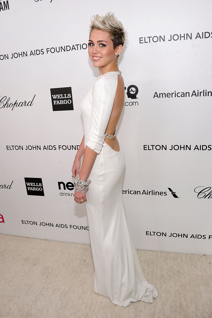 Miley Cyrus wore a backless white dress to join Elton John's viewing party.