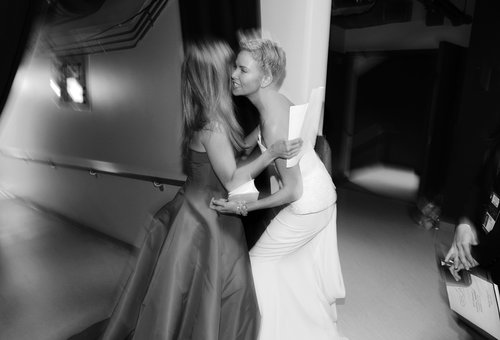Jennifer Aniston and Charlize Theron stopped to embrace backstage.