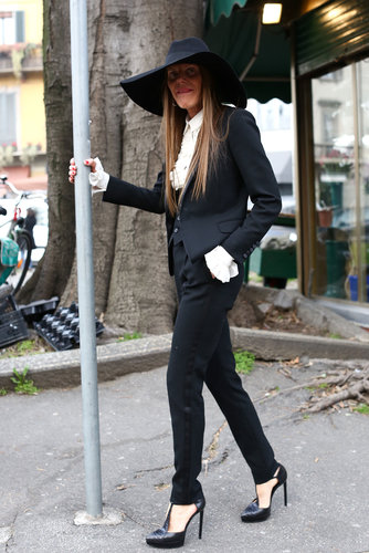 Anna Dello Russo buttoned up in more conservative suiting, but with a more dramatic hat to finish it off.