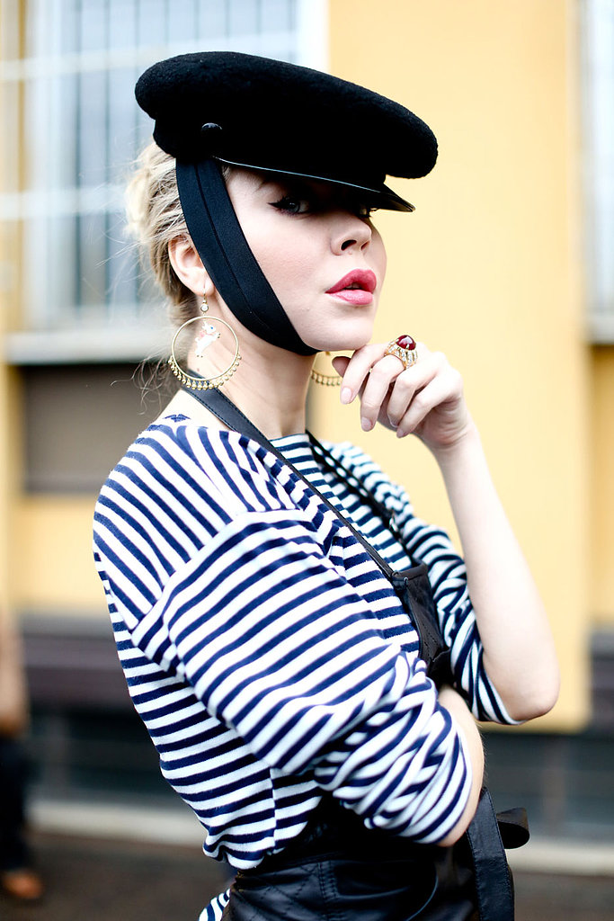We spy a flicked-out cat eye and baby-pink lipstick under that chapeau.
