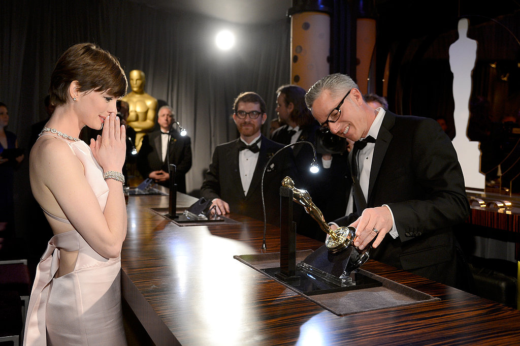 Anne Hathaway watched as her name was etched into her Oscar at the Governors Ball.