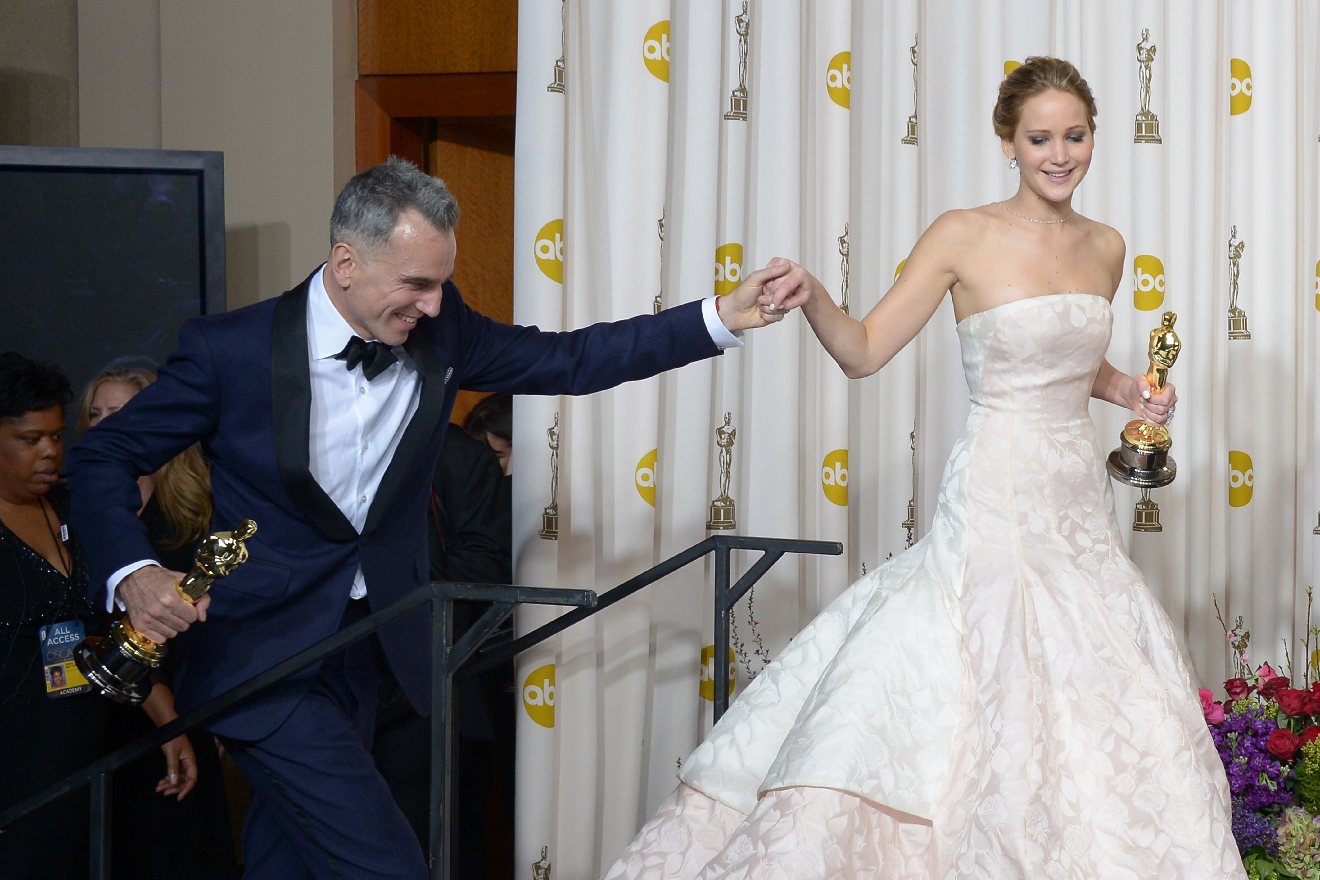 Daniel Day-Lewis gave Jennifer Lawrence a hand in the press room.