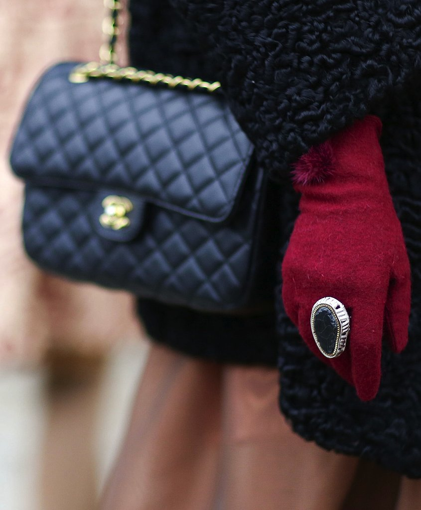What's more eye-catching? The Chanel bag lingering in the backdrop or the stone statement ring and red gloves? We think both.