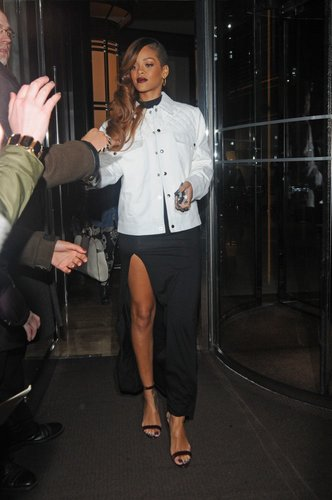 Rihanna exited a London hotel rocking a black maxi dress with a thigh-high slit and a boxy white quilted jacket.