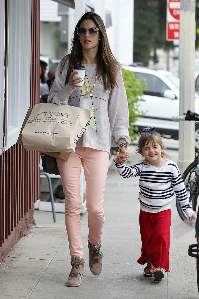 Alessandra Ambrosio worked salmon-pink jeans with Ash wedge sneakers and a star-print sweater while on mommy duty in LA.