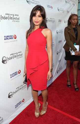 Freida Pinto's little red Rachel Roy dress featured a ruffle skirt that gave it that special something. Gold ankle-strap sandals, a gold cuff, and a box clutch completed her LA party style.
