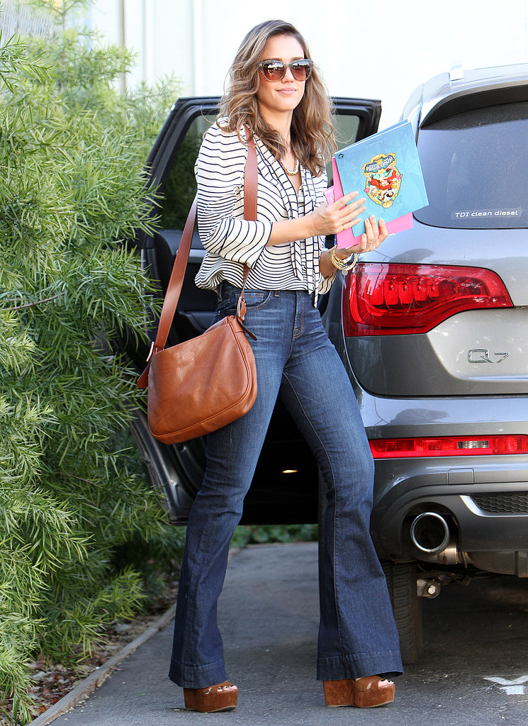 Jessica Alba posed in a striped Tory Burch blouse, denim trousers, and suede wedges outside of her Santa Monica office. To wrap up her office-ready look, it's all about her cat-eye shades and leather Longchamp bag.