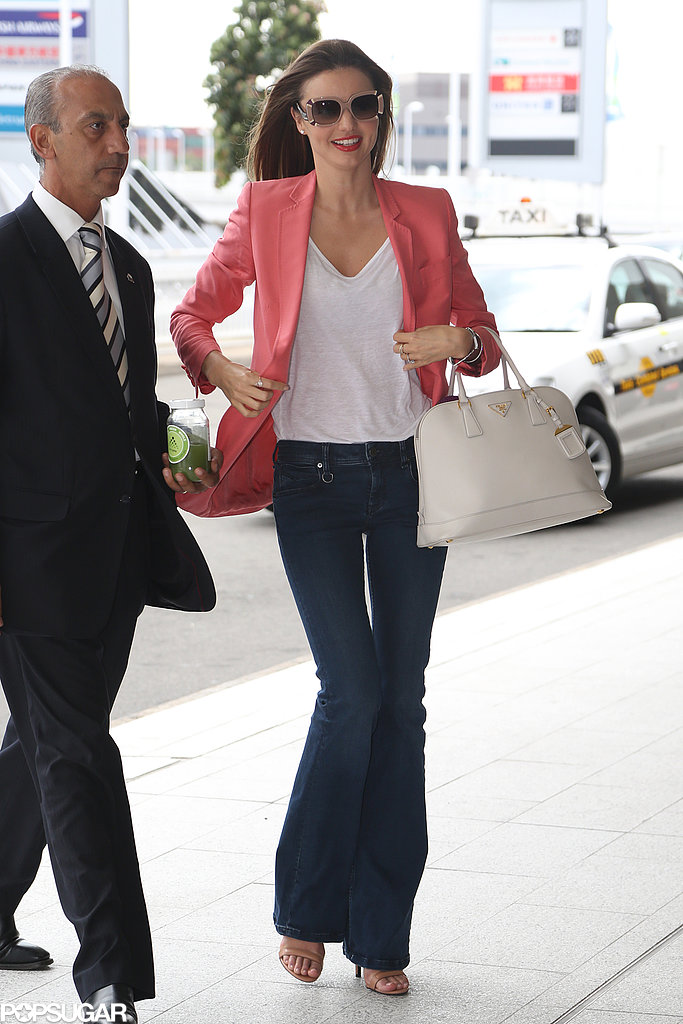 Miranda Kerr landed in Sydney looking bright in a coral blazer, a white V-neck tee, wide-leg jeans, finished with beige sunglasses, nude sandals, and a white Prada bag.
