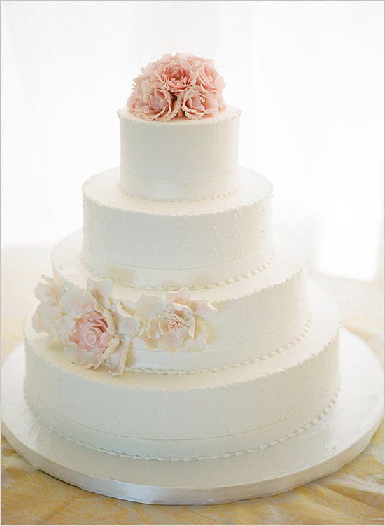 Love the idea of a traditional cake but don't want all the fuss that comes with it? Then you'll want to take note of this sleek version — with just a few beaded details and flower accents, it's both clean and sophisticated.  Photo by Kristin Sweeting via Wedding Chicks