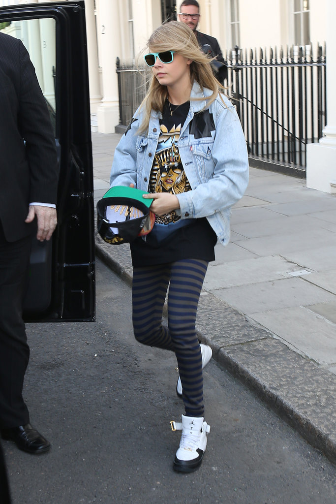 Cara Delevingne threw a Levi's denim jacket over her printed tee, striped leggings, Nike Air Jordan sneakers, and green sunglasses in London.