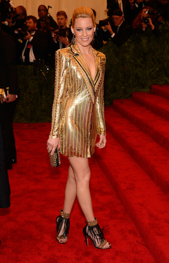 Elizabeth Banks had a golden moment in her Atelier Versace gold metallic blazer dress, Kara Ross jewelry, and black-and-gold fringed Brian Atwood sandals.
